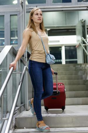 Uśmiechnięta dziewczyna w swobodnym stroju spacerująca z bagażem na stacji metra Zdjęcie Seryjne