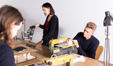 Young architects working on machine tools, creating new architectural model in design bureau
