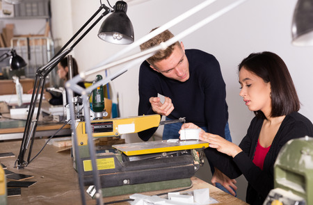 Young teacher helping girl making elements on scroll saw for architectural model in university workshop 写真素材