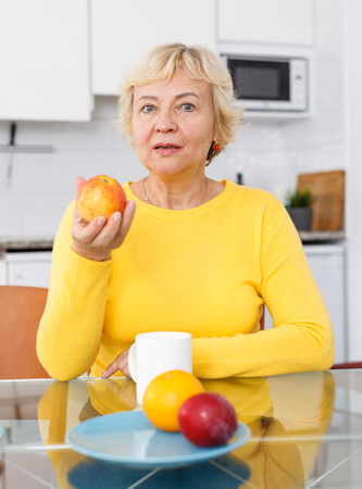 Portrait of beautiful senior woman with plate of fruits at kitchen