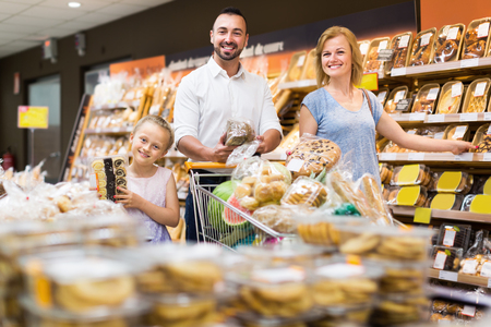 Smiling  parents with girl selecting bread and sweets from rack in grocery store. Focus on girl Stok Fotoğraf