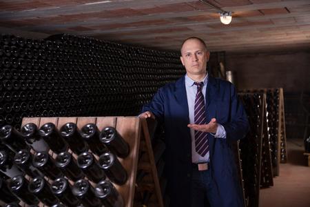 Сonfident winemaker inviting to wine cellar, demonstrating bottles with aging wine on racks Reklamní fotografie