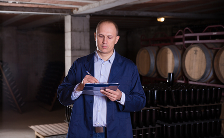 Confident male winemaker working in wine cellar, taking notes on clipboard