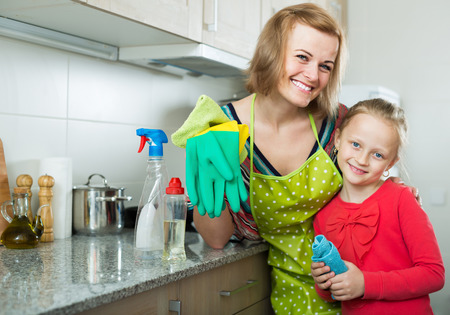 Mature happy mom and little kid cleaning at kitchen together
