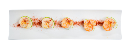 Top view of grilled shrimps on rice balls served on white plate with lime and dried saffron threads. Isolated over white background