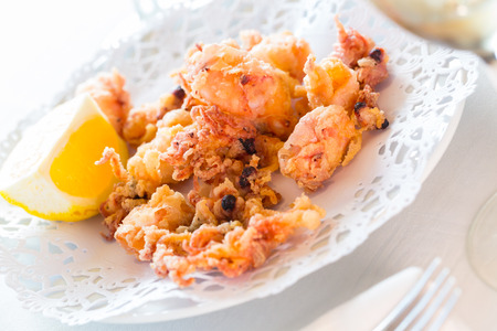 Spanish dish chipirones, small squid battered and fried, served with lemon