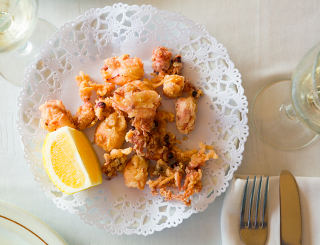 Chipirones, battered fried baby squid served with lemon on white plate