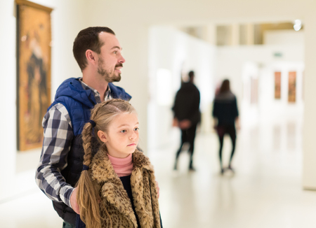 Adult man and daughter enjoying expositions in museum Banque d'images