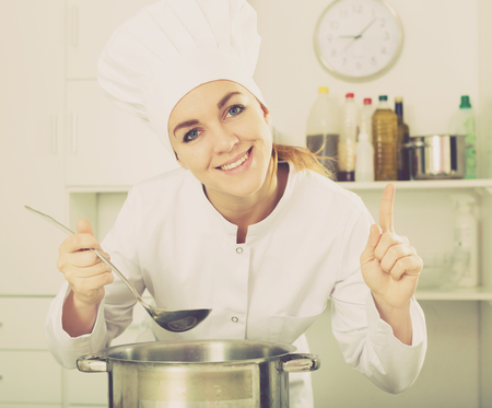 Smiling woman cook tasting delicious dishes in kitchen