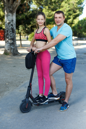Happy friendly family of father and preteen girl wearing sports clothes riding scooter outdoors