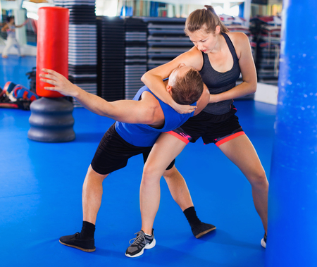 Strong bold   woman  is training captures with man on the self-defense course in gym.