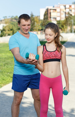 Slim tweenager girl performing physical exercises with dumbbells during daily workout with her father outdoors