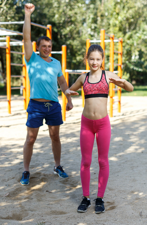 Happy tween girl stretching together with father during training outdoors in summer day Banque d'images
