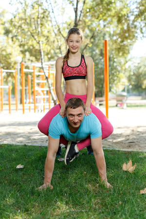 Smiling athletic man doing push-ups with preteen daughter sitting on his back during workout outdoors in sunny day Foto de archivo