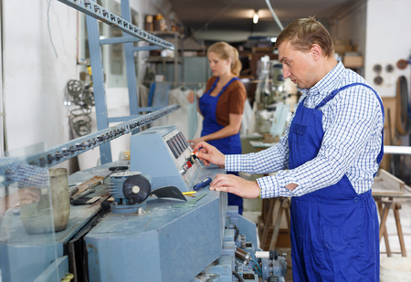 Confident male glazier working on glass straight line chamfering machine in workroom
