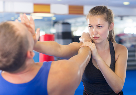 Happy woman is fighting with trainer on the self-defense course for woman in sport club Stock Photo