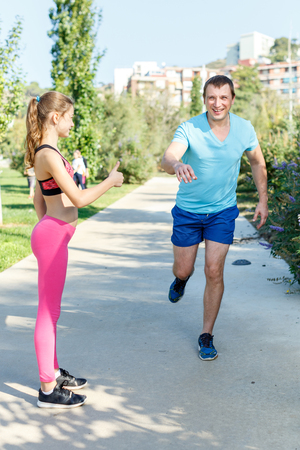 Smiling athletic man running during workout with his preteen daughter outdoors in summer day