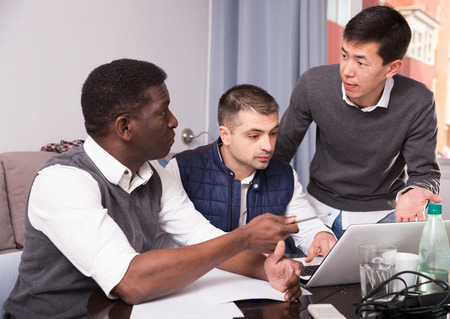 Concentrated men working with documents while sitting at table at home Stock Photo