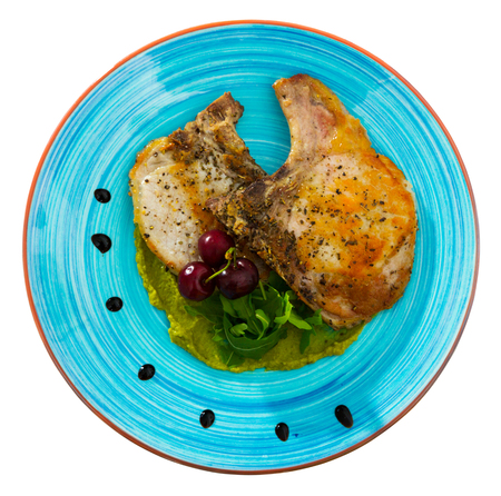 Top view of roasted pork rib steaks served with guacamole sauce decorated arugula and ripe cherry. Isolated over white background