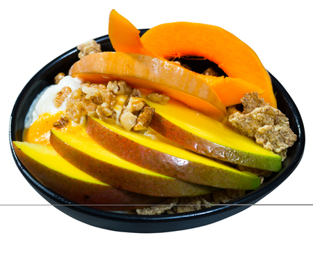 Healthy breakfast of mango slices and baked pumpkin with yogurt, cereals, nuts and dried fruits. Isolated over white background