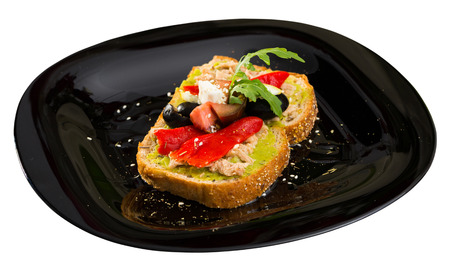 Sandwich with canned tuna, guacamole, olives, arugula and Feta cheese is tasty dish. Isolated over white background