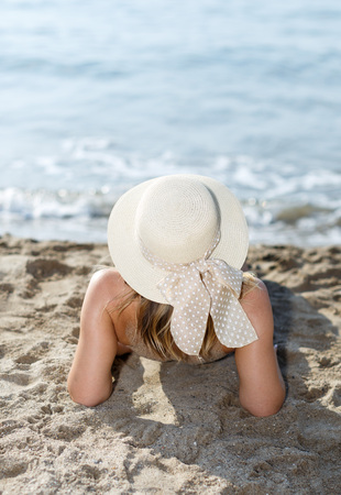 Closeup of young woman in swimsuit and hat  taking sunbath at sea shore