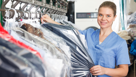 Girl working in modern dry cleaner, checking clean clothes hanging on rack