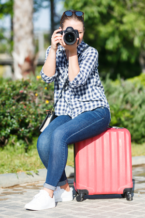 Modern woman traveler strolling with luggage around city, making photo of sights