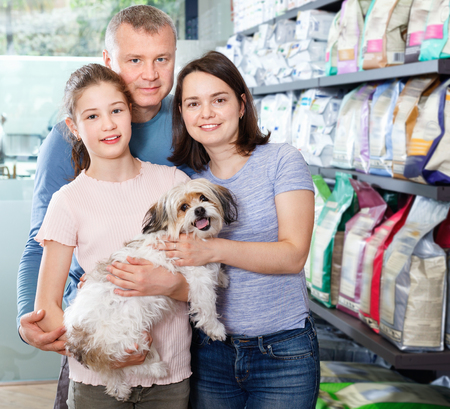 Portrait of friendly cheerful positive glad family with their puppy during visit of pet shop Фото со стока