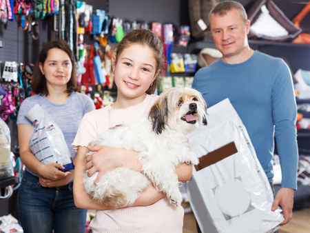 Portrait of cheerful girl with havanese pup while shopping with parents in pet store