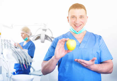 Smiling male professional dentist posing at dental clinic with fresh yellow apple in hands Stock Photo