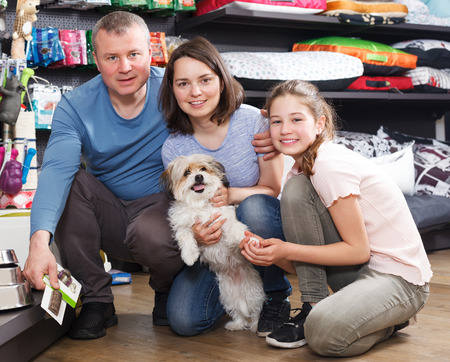 Portrait of happy family with little dog in store of pet accessories