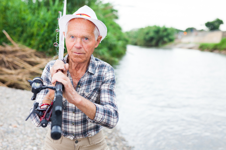 Portrait of mature fisherman standing at river beach with fishing rod