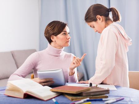 Mother does remarks daughter for incorrectly solved school homeworks Reklamní fotografie