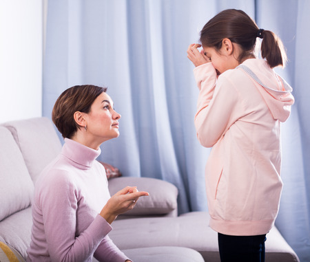 Young mother reprimands her daughter for wrong acts and bad behavior