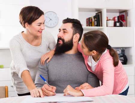 Young parents signing papers for new house with their daughter