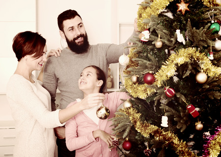 Parents and daughter putting decorations on Christmas tree at home