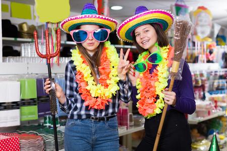 Portrait of modern comically dressed girls joking in festive accessories shop