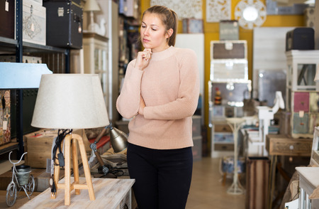 Female customer looking at torchere in the furniture store before the buying Zdjęcie Seryjne