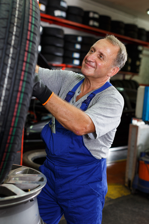 Professional male mechanician restoring tire and disc of car wheel in auto repair shop