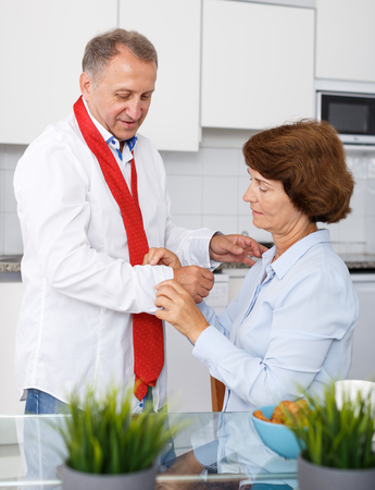 Portrait of mature woman adjusting tie to man at kitchen table at home 免版税图像