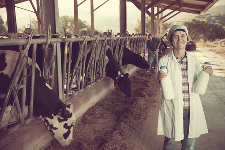 Portrait of woman quality expert who is standing at the cow farm.