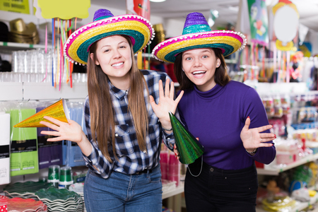 Comically dressed happy female friends having fun in carnival outfits store