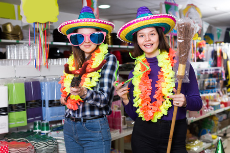 Portrait of happy nice comically dressed girls joking in festive accessories shop