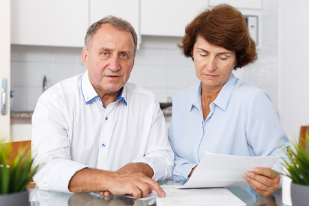 Unhappy mature family couple sitting at kitchen table with documents together