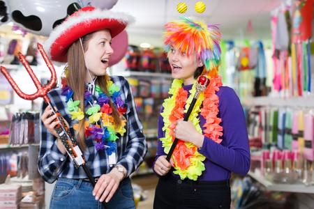 Portrait of smiling comically dressed girls joking in festive accessories shop Reklamní fotografie