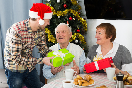 Elderly husband and wife exchange holiday Christmas gifts with grandson