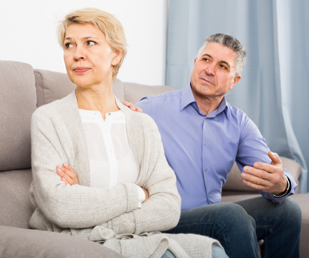 annoyed mature couple quarreling at home with each other and take offense