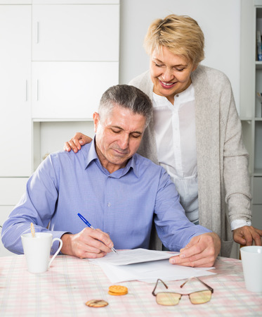 attentive mature couple at table attentively study documents and sign agreement