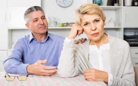 european husband and wife arguing with each other and try to resolve family conflict at table
